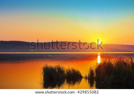 Beautiful sunset over calm lake. Dusk time. reeds at foreground