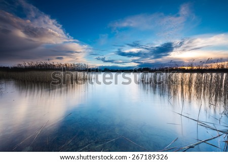 Beautiful sunset over calm lake in Mazury lake district. After sunset sky reflecting in water, calm vibrant landscape. - stock photo