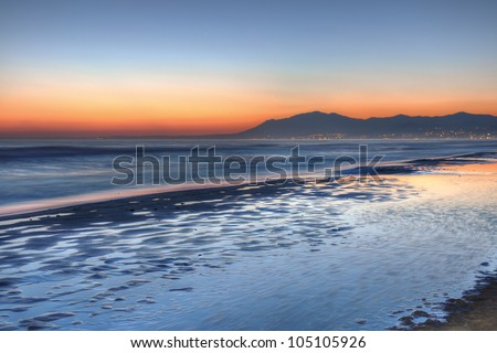 Beautiful sunset over Costa del Sol.The Costa del Sol is a region in the south of Spain comprising the coastal towns and communities along the Mediterranean coastline of the M�¡laga province. - stock photo