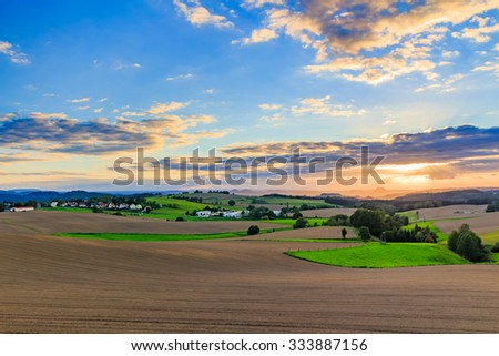 Beautiful sunset over countryside landscape of rolling hills with sun beams piercing sky and lighting hillside - stock photo