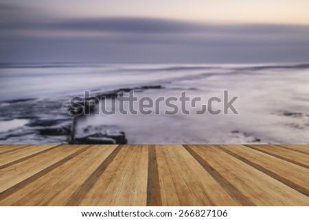 Beautiful sunset over Kimmeridge Bay Jurassic Coast England with wooden planks floor - stock photo
