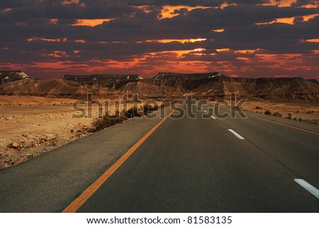 Beautiful sunset over mountains and highway running through Ramon crater in Israel. - stock photo