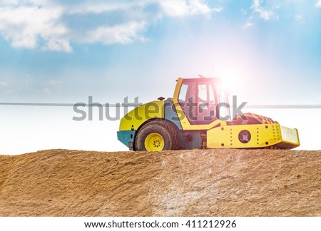 Beautiful sunset over the compactor working on the new road construction site - stock photo