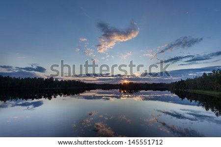 beautiful sunset over the forest lake with reflections - stock photo