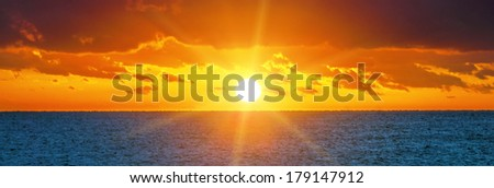 Beautiful sunset over the ocean, panoramic view. - stock photo