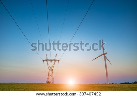 Beautiful sunset over the powerline on the field - stock photo