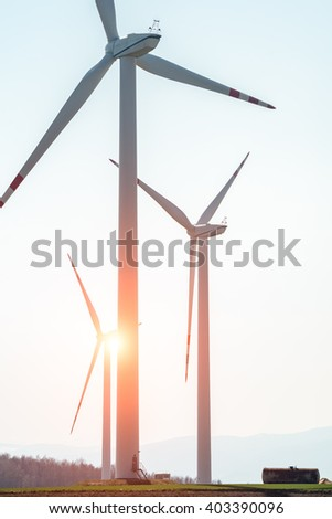 Beautiful sunset over the windmills on the large green field
