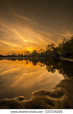 Beautiful sunset reflection over wild river - stock photo