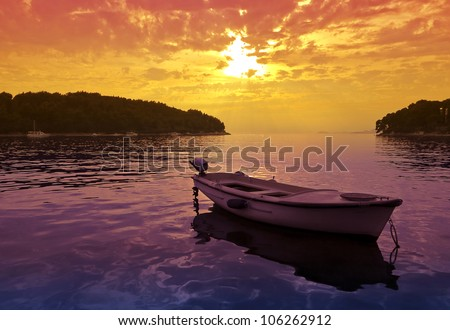 Beautiful Sunset scene with a small boat - stock photo