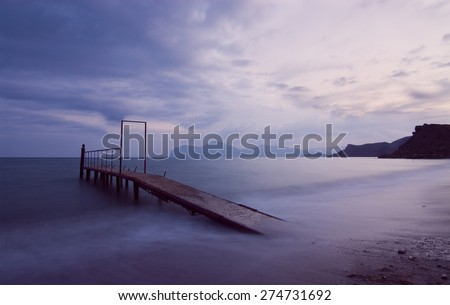 Beautiful sunset seascape with old pier and mountains in the background. - stock photo