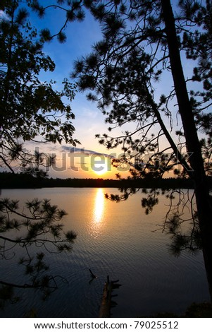 Beautiful sunset seen through pine trees over a northwoods Wisconsin lake. - stock photo