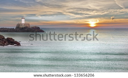 Beautiful sunset with lighthouse in atlantic ocean, france - stock photo