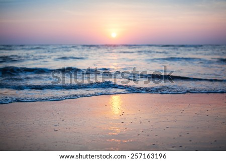 Beautiful sunset with wave at the beach. Focus on wave. - stock photo