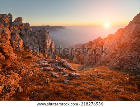 Beautiful sunsets in the autumn alpine mountains. The cloudy sky and fog above the sea. Mystical landscape. It is photographed from a tourist track.