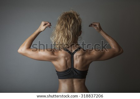Beautiful super fit young woman showing off her perfect muscular body. Fitness model. Perfect Slim Body with sturdy back muscles. Studio shot - stock photo