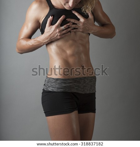 Beautiful super fit young woman showing off her perfect muscular ripped abs. Fitness model. Perfect Slim Body. Studio shot - stock photo