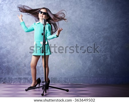 "Beautiful super-star girl in dress and ""MOTHER'S HEELS"" with microphone on grey background"