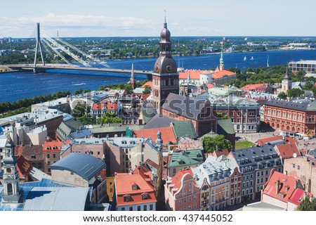 Beautiful super wide-angle panoramic aerial view of Riga, Latvia with harbor and skyline with scenery beyond the city, seen from the St. Peters Church observation tower,sunny summer day with blue sky  - stock photo