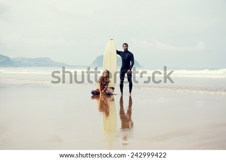 Beautiful surfer couple standing on the beach before their sunday surf lesson, young cute couple of surfers standing on amazing ocean and mountains background - stock photo