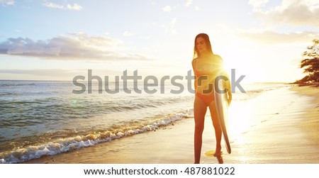 Beautiful surfer girl walking down the beach into the sunset