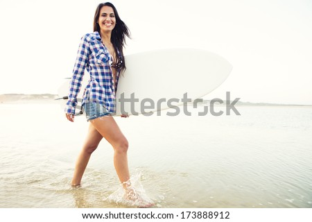 Beautiful surfer girl walking in the beach with her surfboard at sunset - stock photo
