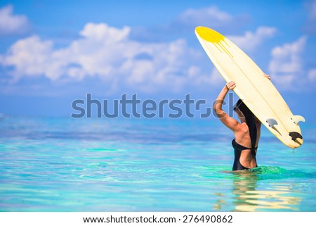 Beautiful surfer woman surfing during summer vacation