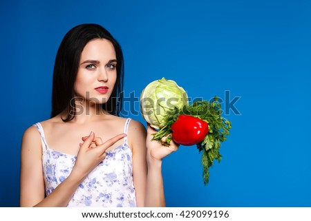 beautiful sweet girl in a simple dress holding a cabbage and centimeter. Concept of healthy eating and weight loss , It shows up on vegetables - stock photo