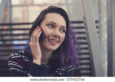 Beautiful sweet girl with blue hair sitting in a room and talking on the phone with friends. - stock photo