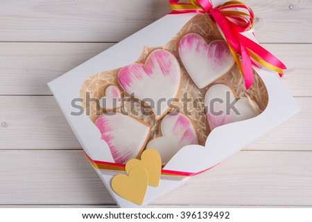 Beautiful sweet hearts in a white box with lovely decoration. Paper hearts with colorful ribbon are perfect combination for a gift. - stock photo