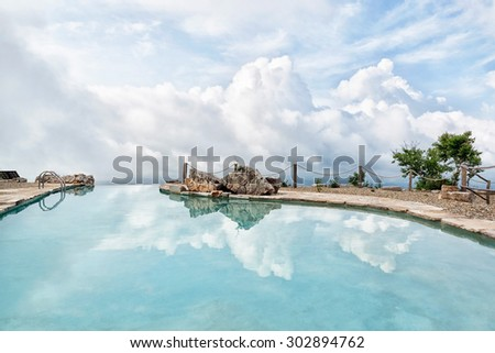 Beautiful swimming pool in the edge of plateau with sky and clouds reflections in the azure calm water - stock photo