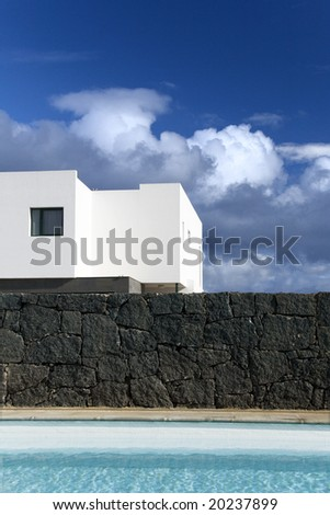 beautiful swimming pool with stone wall amd a house - stock photo