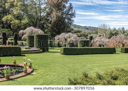 beautiful symmetrical English style garden with beautiful green lawn - stock photo