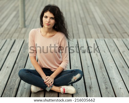 Beautiful tall girl with long hair brunette in jeans sits on wooden planks - stock photo