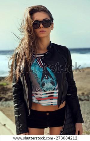 Beautiful tall slim stylish girl at stormy ocean coast. Sexy fashion portrait. - stock photo