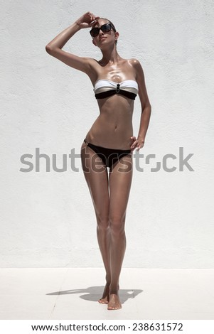 Beautiful tan female model posing in bikini and sunglasses. Against white wall. - stock photo