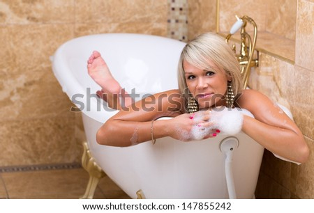 Beautiful tanned girl is taking a luxurious bubble bath - stock photo
