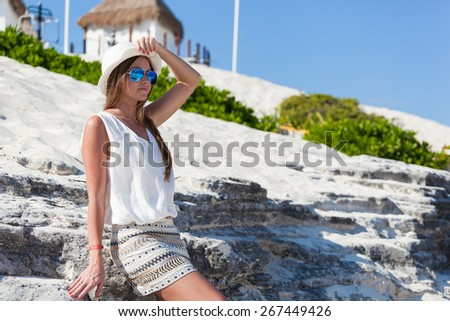 Beautiful tanned woman posing rock's background, enjoying summer vacation - stock photo
