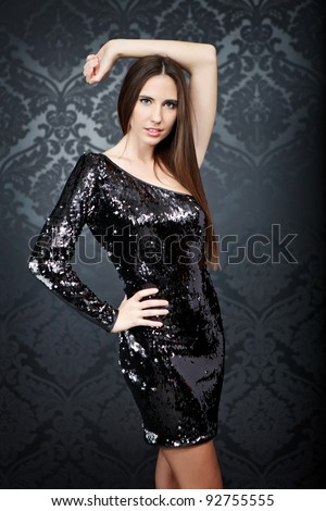 beautiful tanned woman wearing in sequin black cocktail dress standing - stock photo