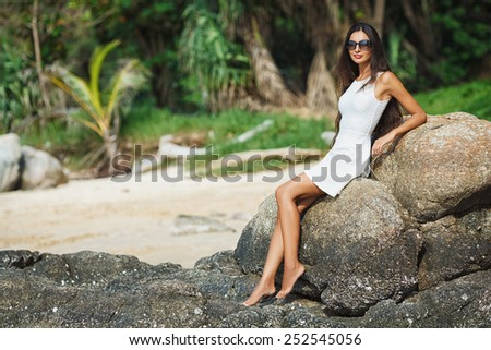 beautiful tanned woman wearing white dress sitting on stone - stock photo