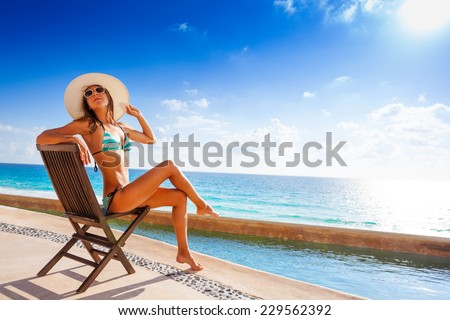 Beautiful tanned woman with sunglasses sunbathes - stock photo