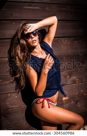 beautiful tanned young woman in bikini and navy blue summer shirt against wooden wall outdoor shot hot summer day - stock photo