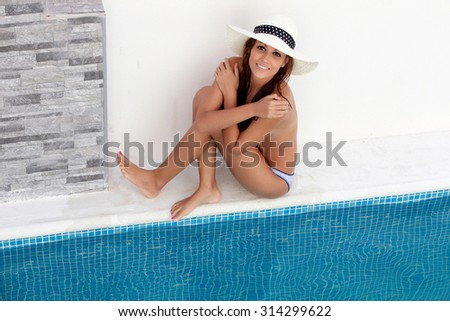 Beautiful tanned young woman with hat sitting poolside - stock photo
