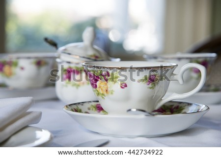 Beautiful tea cup painted with roses, shallow focus, indoor soft light - stock photo