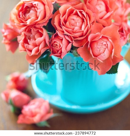 Beautiful tea roses in a blue cup on a table. - stock photo
