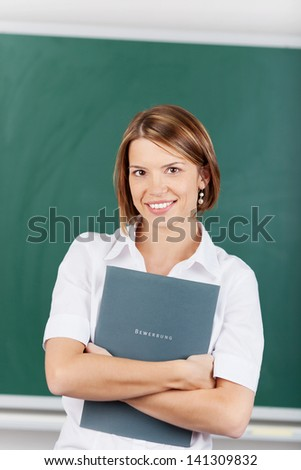 Beautiful teacher holding a lesson plan inside the classroom