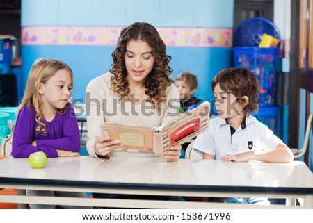 Beautiful teacher reading book while children listening to her in classroom