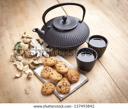 beautiful teapot with chocolate biscuits on wooden table, delicious breakfast - stock photo