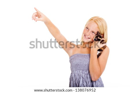 beautiful teen girl holding pet kitten and pointing on copyspace - stock photo