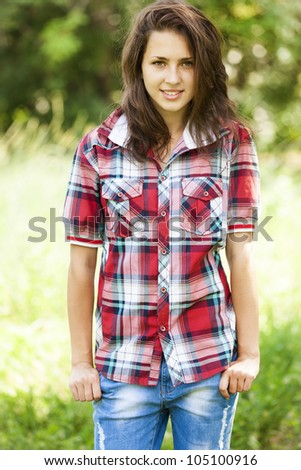 Beautiful teen girl in the park at green grass. - stock photo