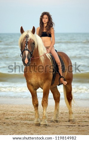 Beautiful teen girl riding a horse on the beach - stock photo